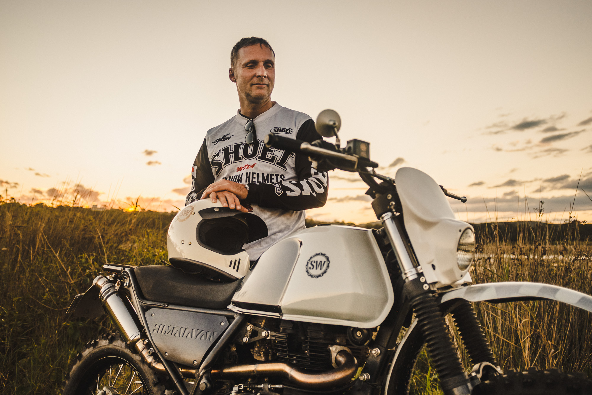 Schlachtwerk's Tommy and his Royal Enfield Himalayan Enduro Custom on a beach at sunset in Sydney