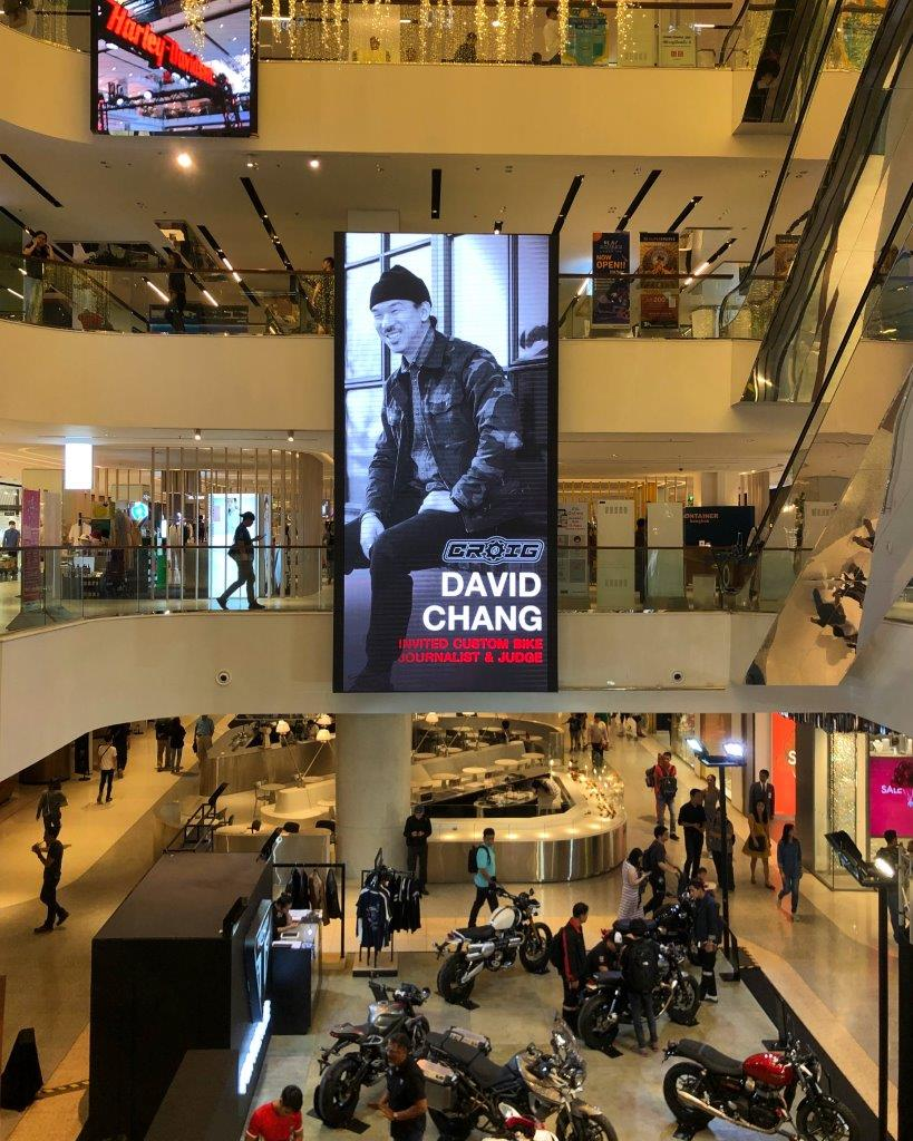 David Chang's photo on a jumbotron screen at a shopping mall