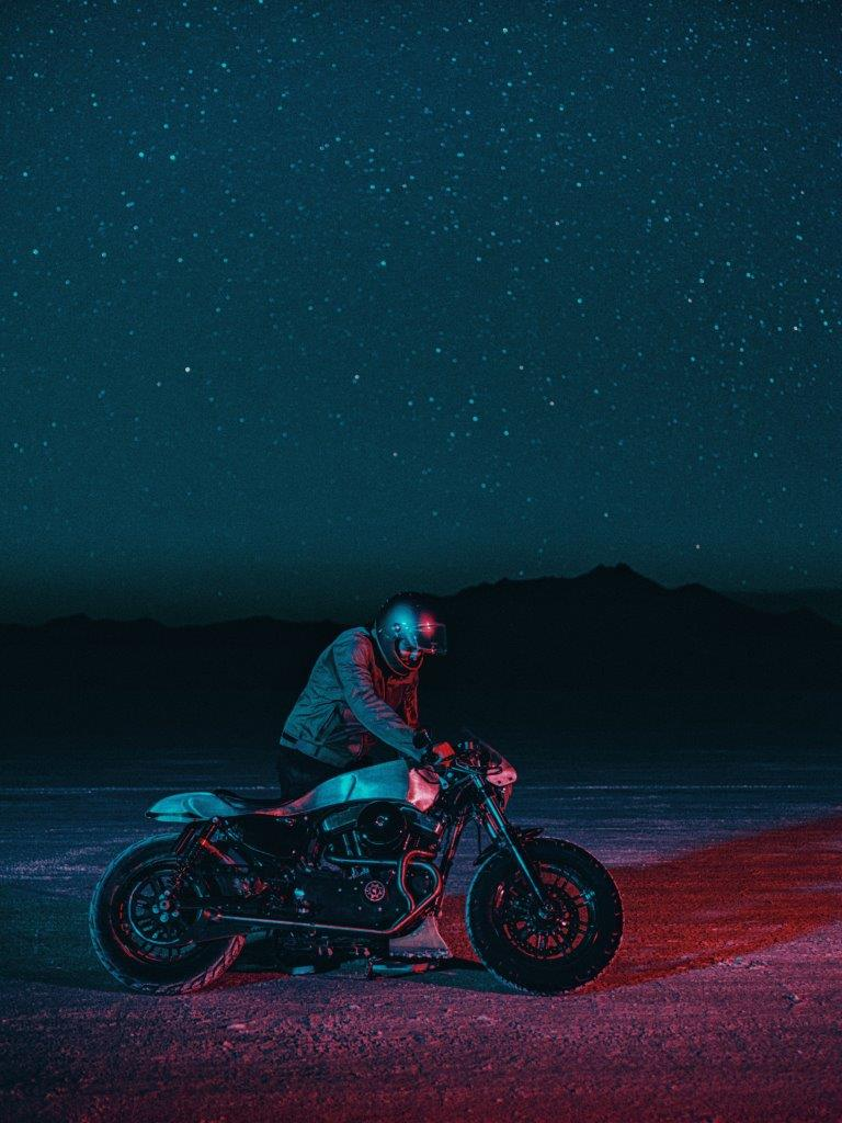 David Chang from Cafe Racers of Instagram on a Harley motorcycle riding on a salt flat at night