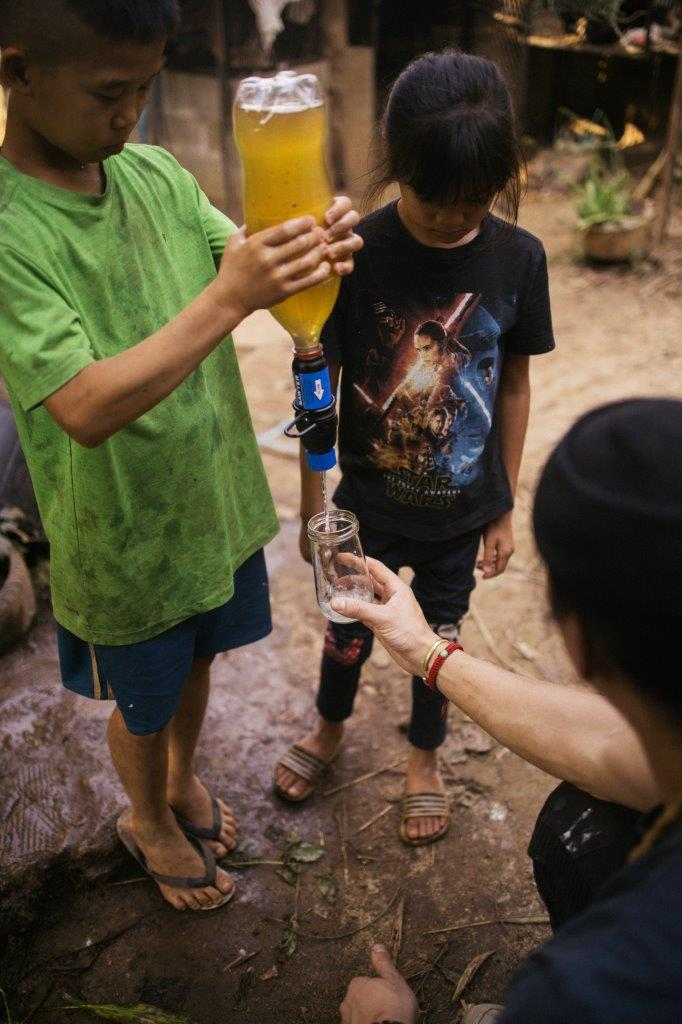 David Chang in Cambodia helping two young children filter dirty water into clean drinking water