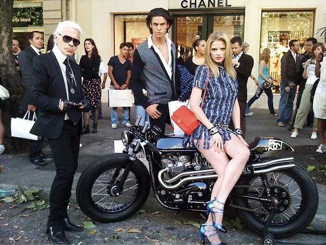 Karl Lagerfeld and two models pose for a photo while standing around a Chanel cafe racer