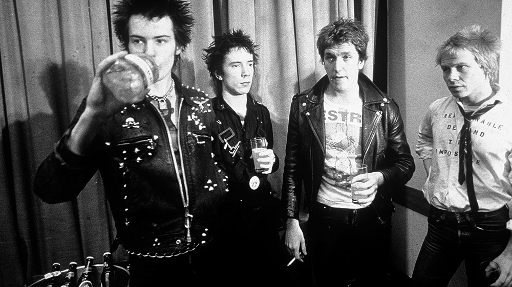 The Sex Pistols pose for a photo while drinking beer in the late 1970s