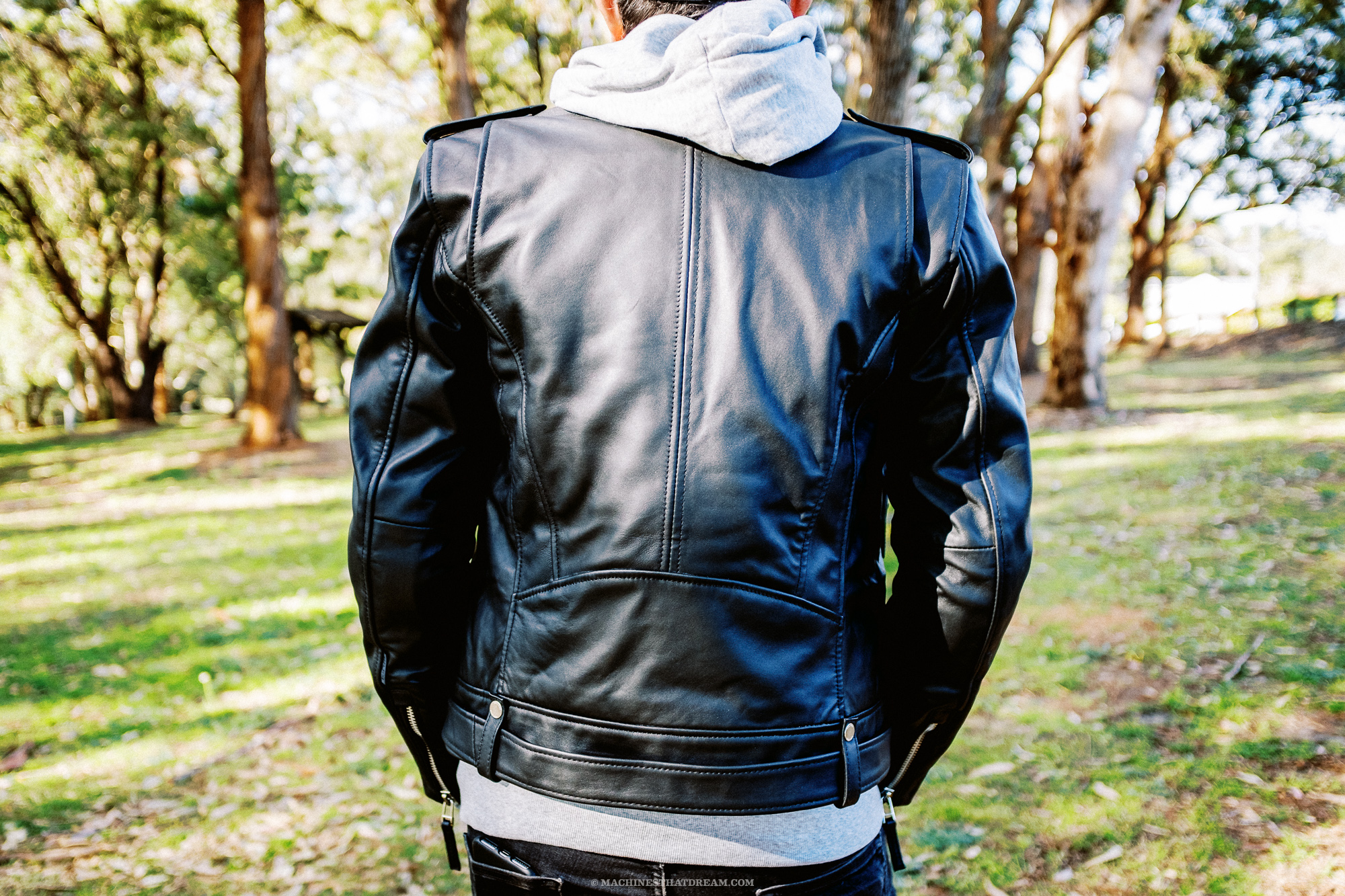 A strange man in a park wearing the Boda Skin's 'Voyager' leather motorcycle jacket