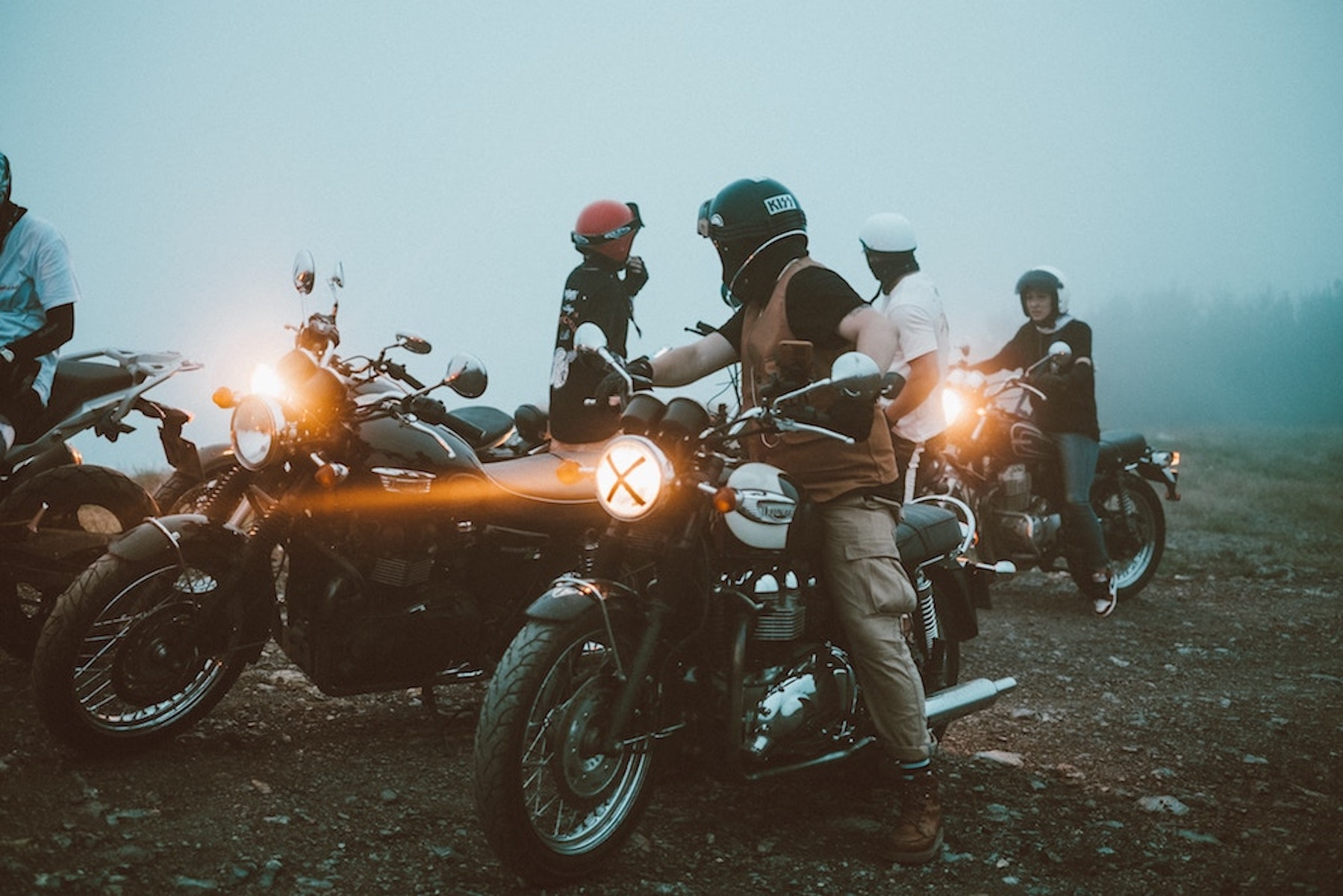 a group of motorcycle riders gather on a foggy morning