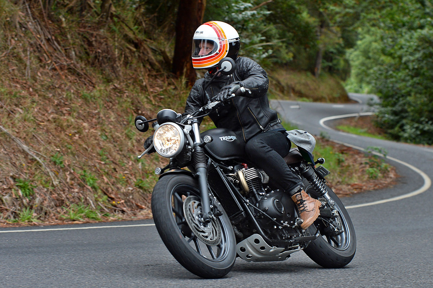 Man rides Triumph motorcycle through forest road in Australia