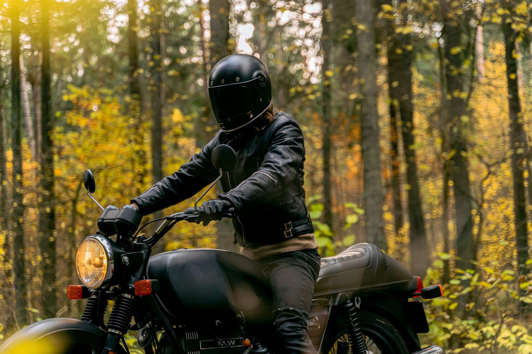 a motorcycle rider dressed in all-black look at the camera in a European forest